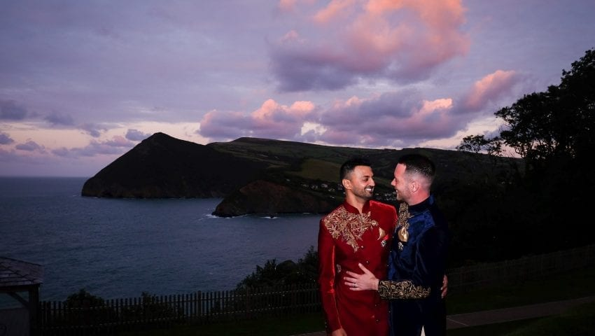 a picture of a married couple standing with a background of sea, cliffs and trees