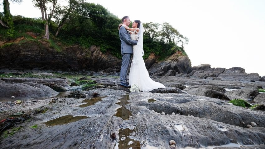 a picture of a married couple standing on rocks holding each other with trees in the background