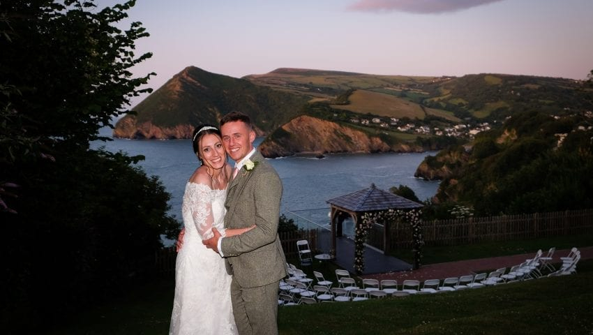 a picture of a couple standing outside with a hill and sea background