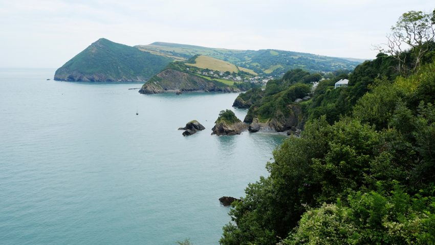 a picture of the sea and surrounding hills with lots of green trees