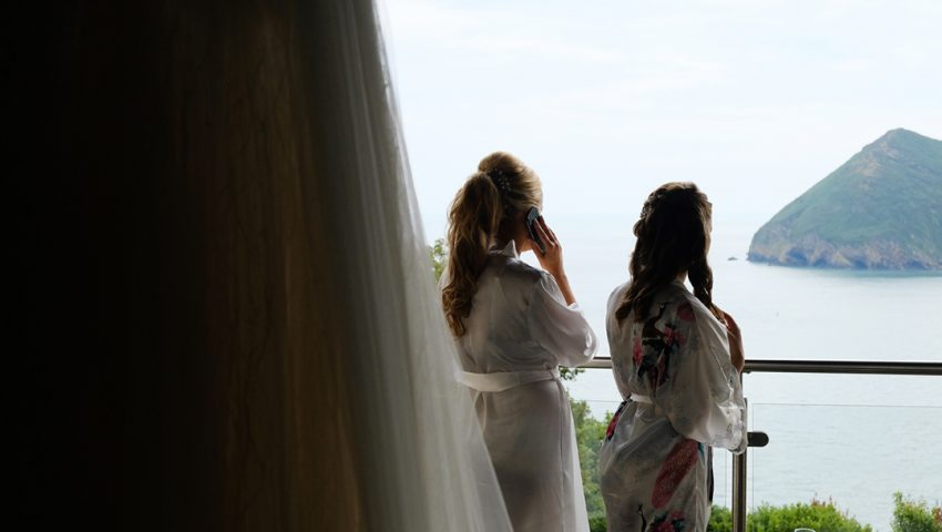 a picture of two girls getting ready on the balcony over looking the sea