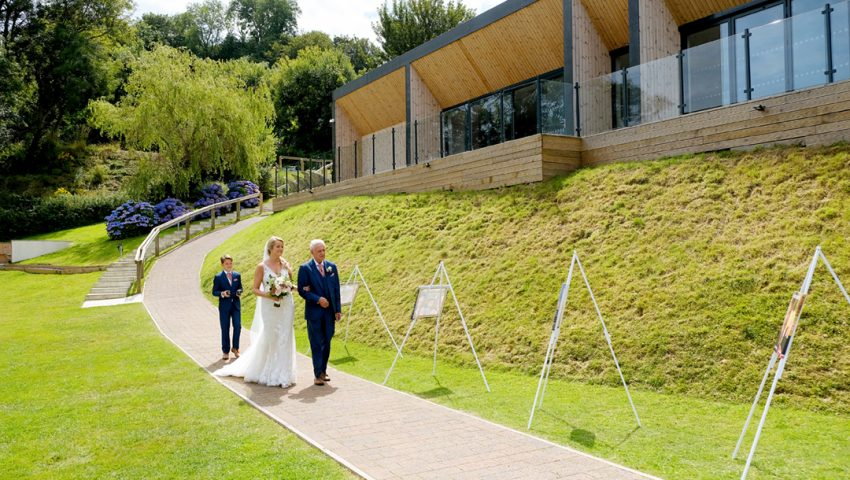 a picture of the bride being walked down the isle with a page boy outside