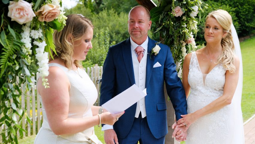 a picture of a couple getting married outside under a floral arch with a woman doing a reading