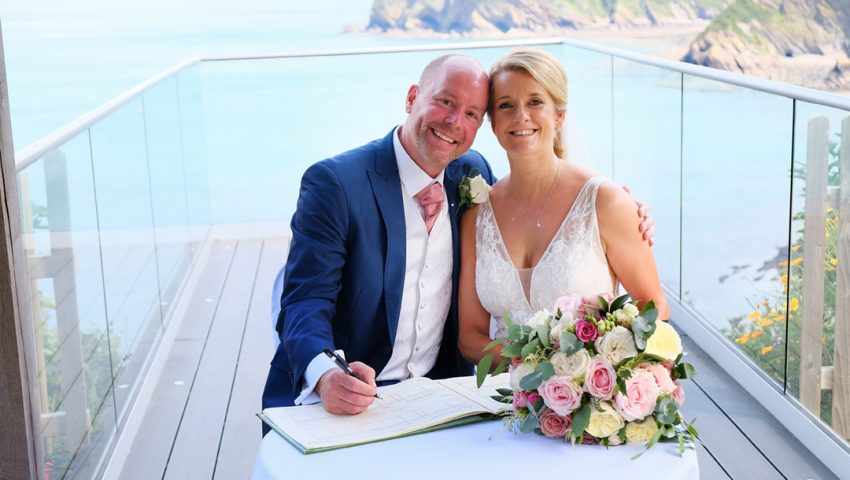 a picture of a married couple sitting down signing the register on the balcony, with the sea in the background and the cliffs surrounding