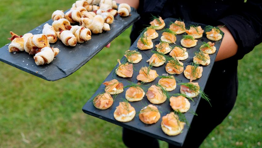 a picture of a waiter holding grey slate serving boards with pastry twists and salmon bellinis