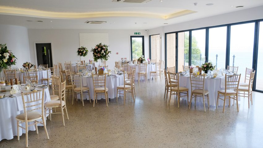 a picture of a wedding dining room with laid white tables and wooden chairs, with floral bouquets, overlooking the sea