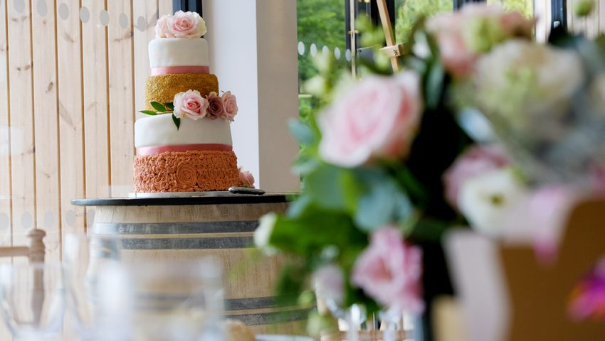 a picture of a four tiered wedding cake on a wooden barrel table with a silver knife and a bouquet of roses