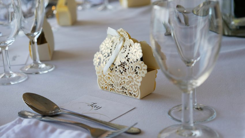 a picture of a laid table for a wedding with glassware and favours