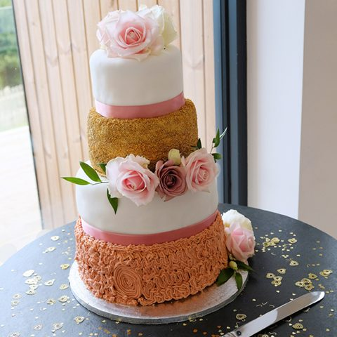 a picture of a four tiered wedding cake on a wooden barrel table with a silver knife