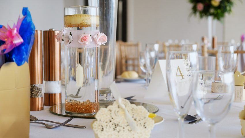 a picture of a laid wedding table with glassware and accessories