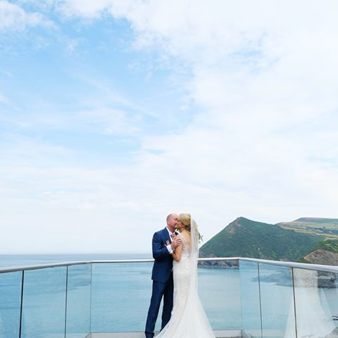 a picture of the bride and groom kissing on a balcony with a seascape and green cliffs in the background