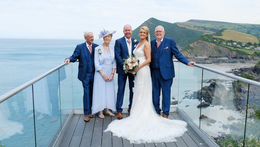 a picture of a family, groom and bride stood on a balcony with the sea and green cliffs in the background