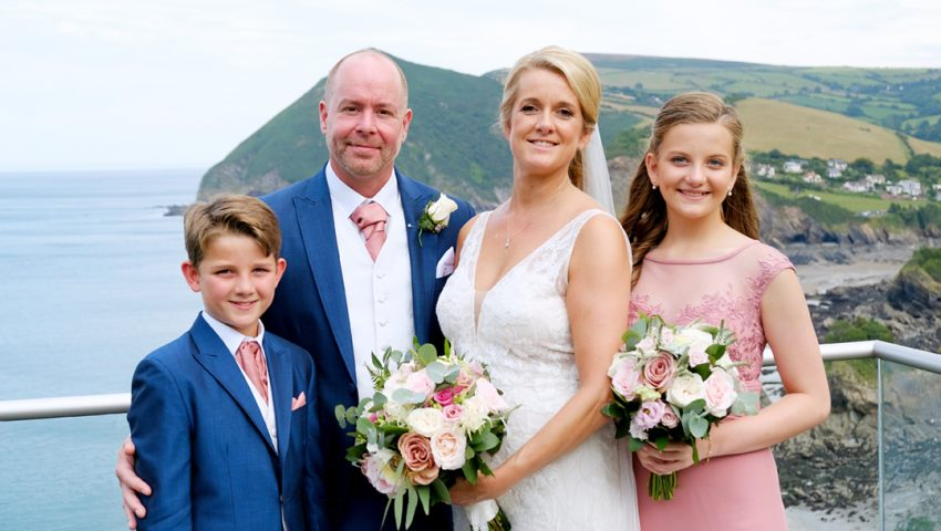a picture of a bride, groom and two children standing infront of sea and green cliffs in the background