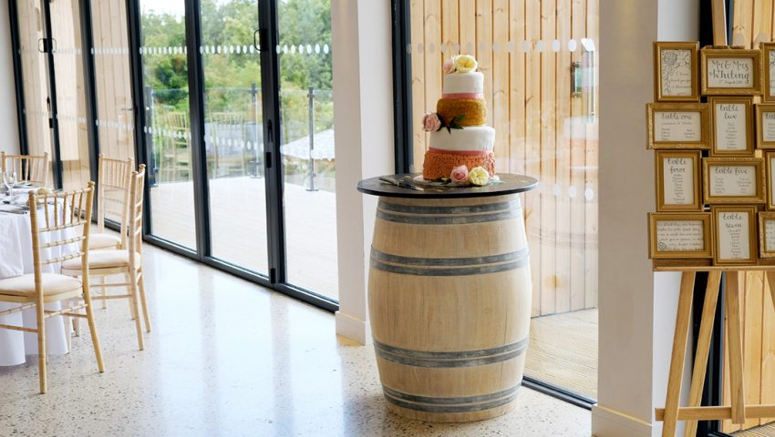 a picture of a 4 tier wedding cake on a wooden barrel table