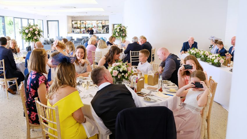a picture of families sat at tables in a wedding reception