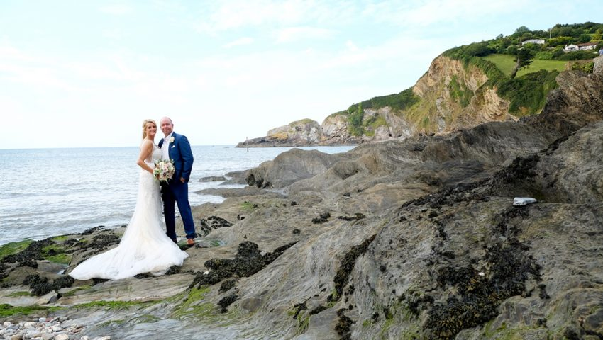 a picture of a married couple standing on rocks with the sea in the background surrounded by rocky cliffs