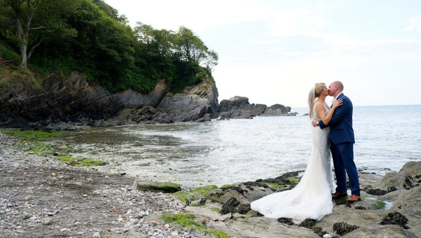 a picture of a wedding couple kissing on the rocks next to a rocky ground, with the sea, trees and cliffs in the background
